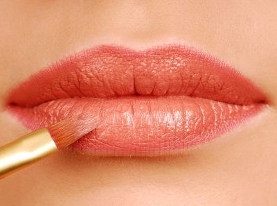 Red lipstick cosmetic brush. Make-up tool. Woman lips close up.